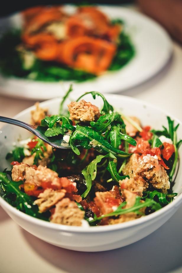 Paximadi vegan mit Rucola und Feta > gehackte Tomaten, Paprika, Kapern, Oliven, Kräuter, Feta und Rucola auf griechischem Knusperbrot.